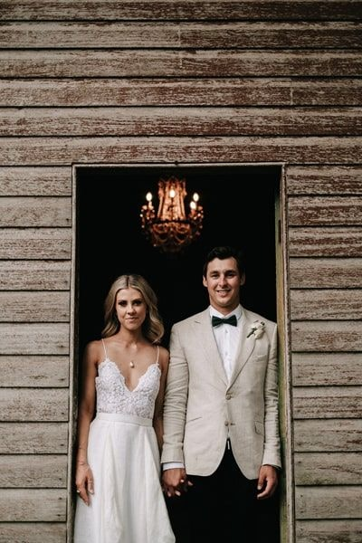 wedding couple holding hands in an open door