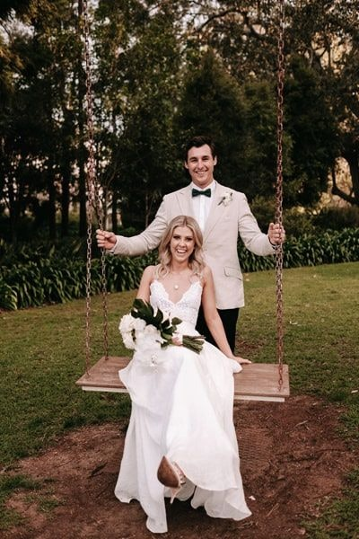 Bride sitting on a swing while the groom pushes her