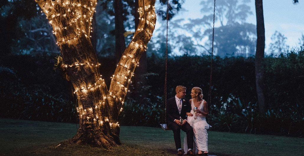 Benjamin and Philippa swinging under a big beautiful tree covered in fairy lights