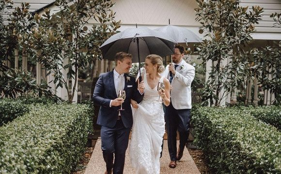 Benjamin and Phillipa holding an umbrella and drinks while walking