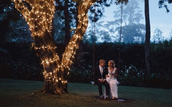 Benjamin and Philippa sitting on swing with fairy lights