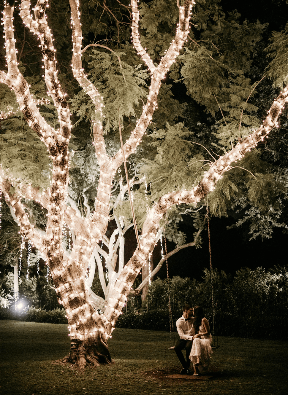 Couple on swing in a garden full of fairy lights