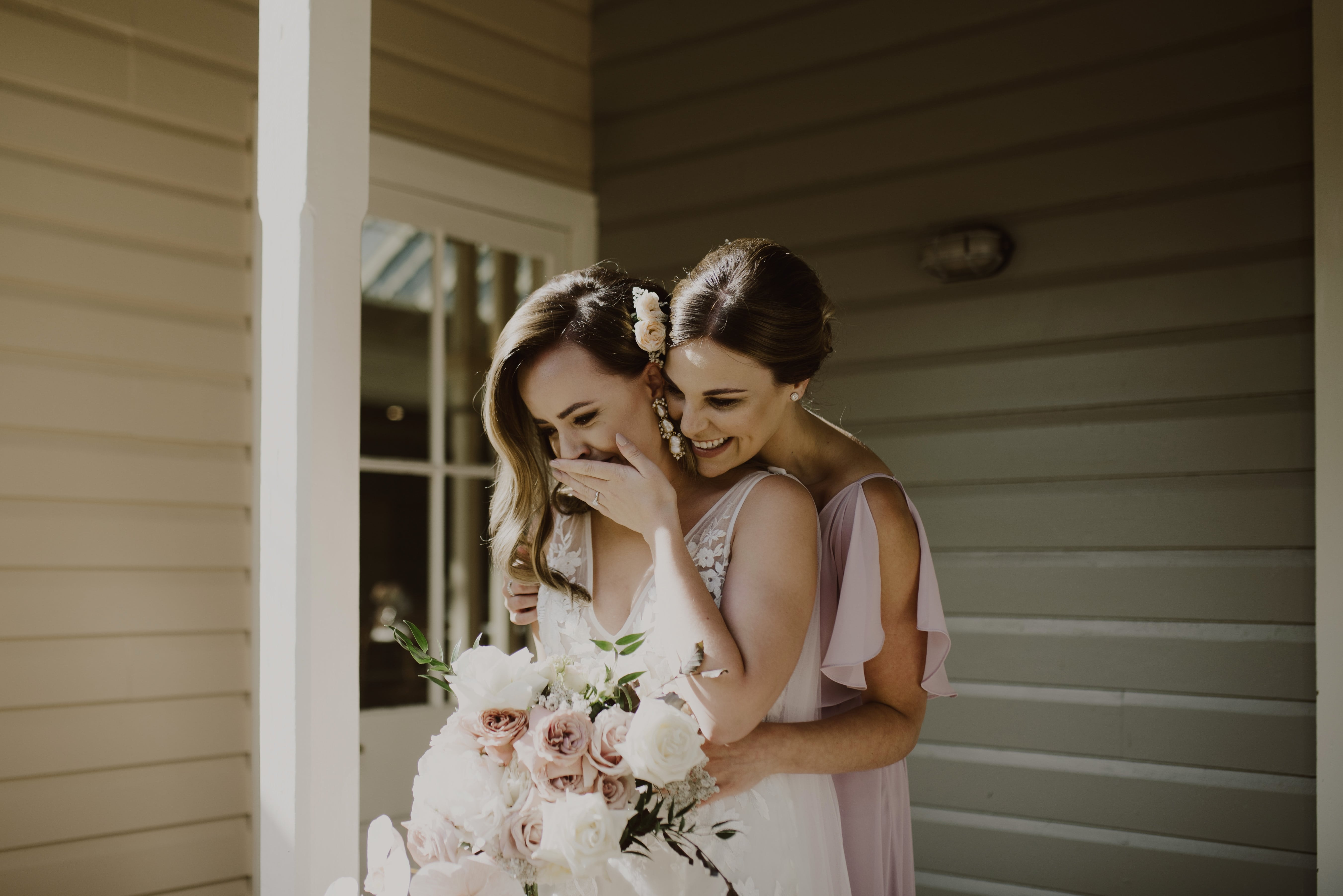 Bride and bridesmaid hug whilst bride cries