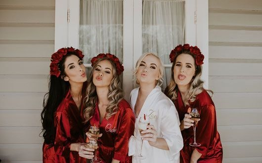 Bride in White Robe with Her Bridesmaids Wearing Red Robes