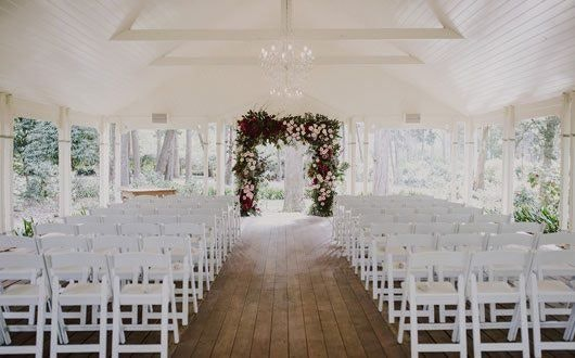 Pink, red and white floral arbour with classic americana chairs