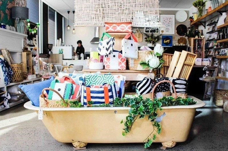 An Antique Bathtub Decorated with Plant and Handbags Inside