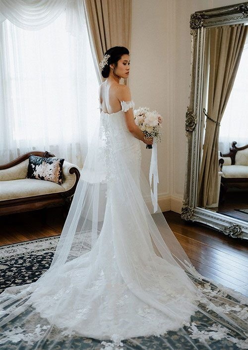 Bride in brides retreat with sweeping sheer cape