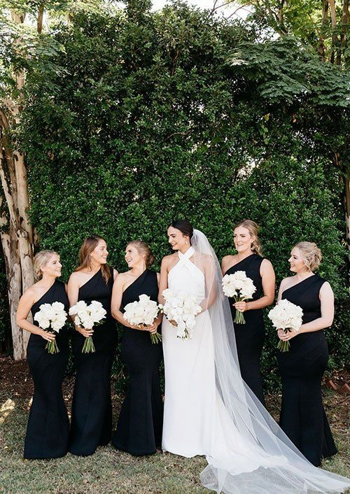 Bride in white stands amongst her bridesmaids in black