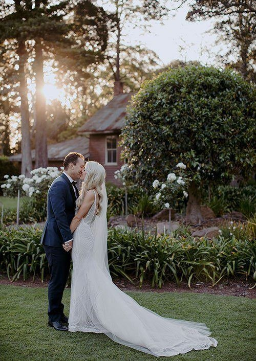Bride and groom kiss in the gardens at Gabbinbar Homestead