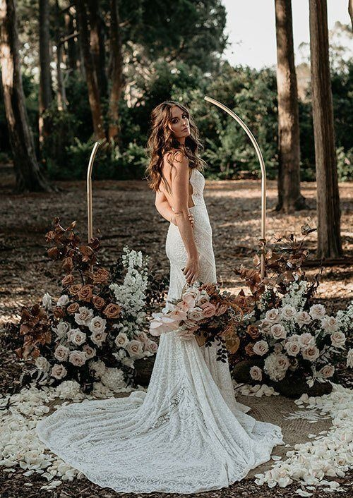 Bride in backless bridal gown with rust and soft pink roses