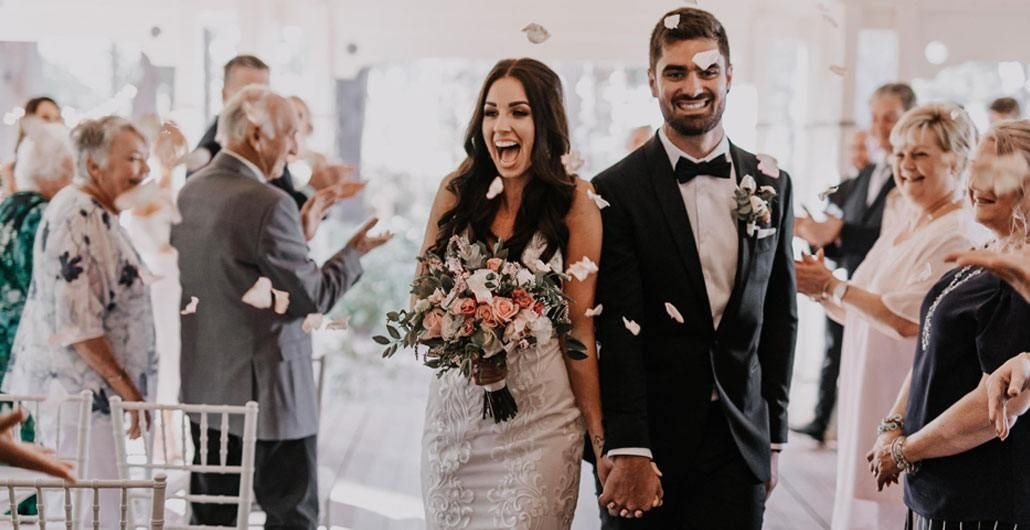 Groom and Bride Holding Hands While Walking in The Middle of The Crowd
