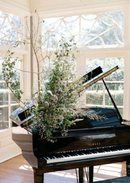 Baby grand piano decorated with bunches of wild flowers