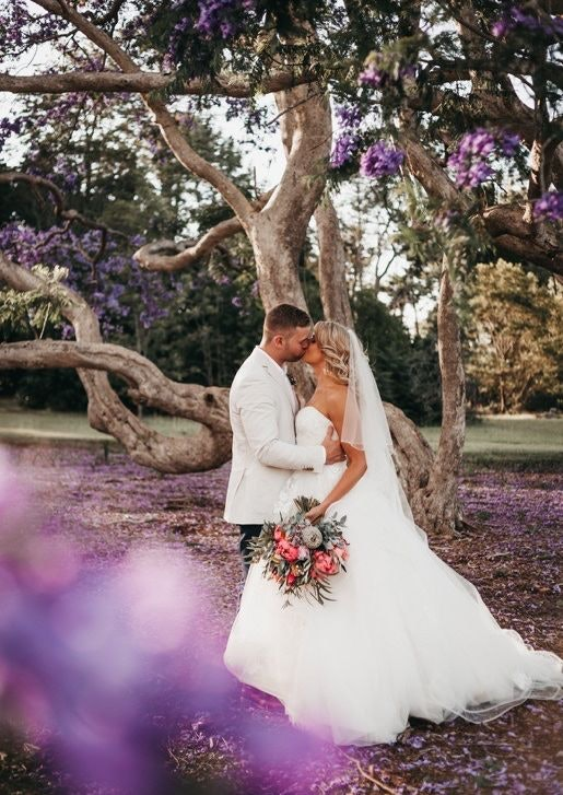 Wedding couple with purple jacarandas