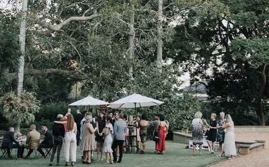 Guests mingle outside after wedding ceremony under white umbrellas