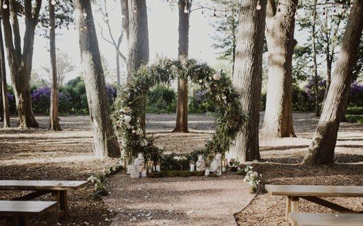 Rustic country wedding arbor with green foliage and candles