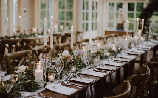 Candles and green foliage on table