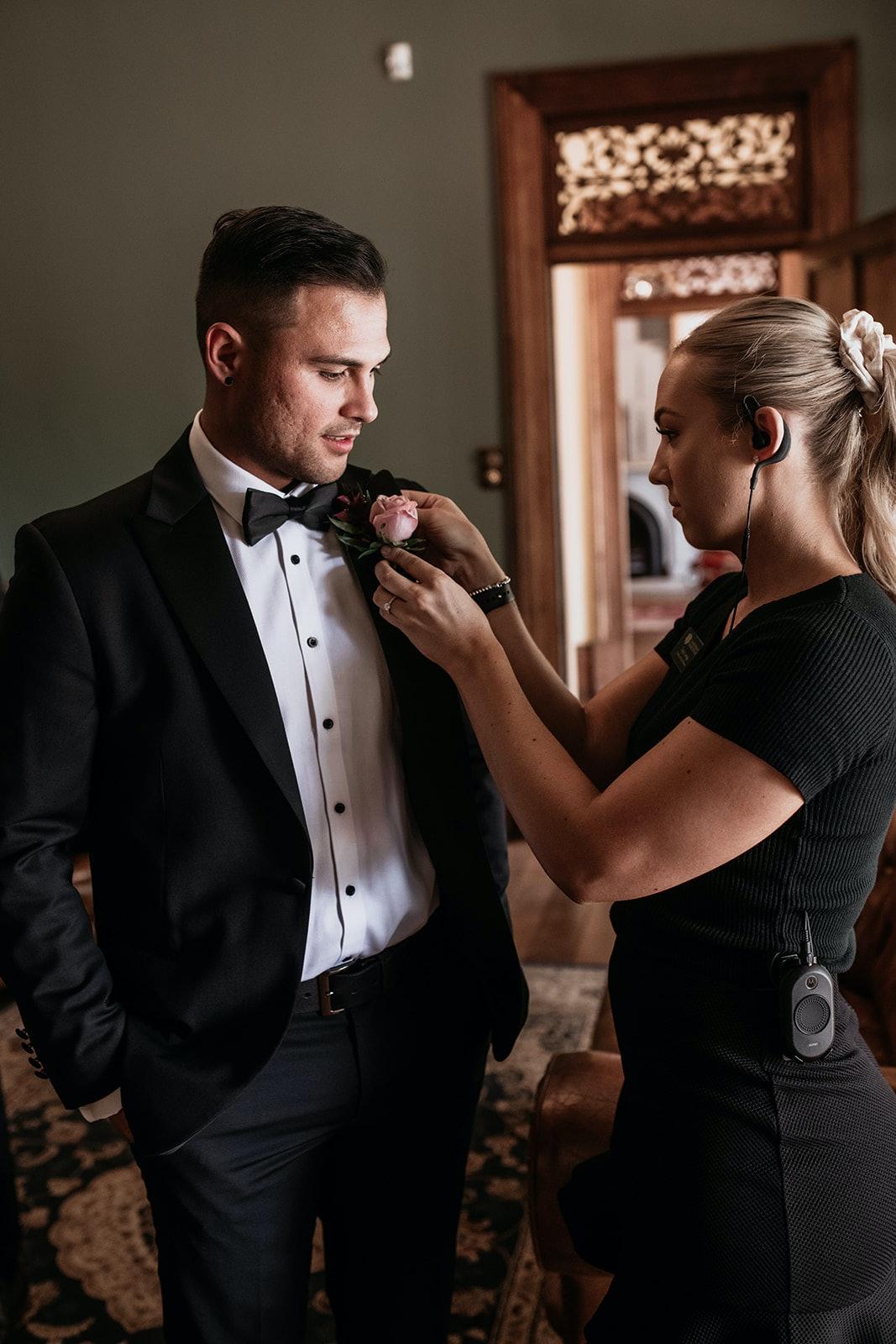 wedding planner adjusts buttonhole on groom