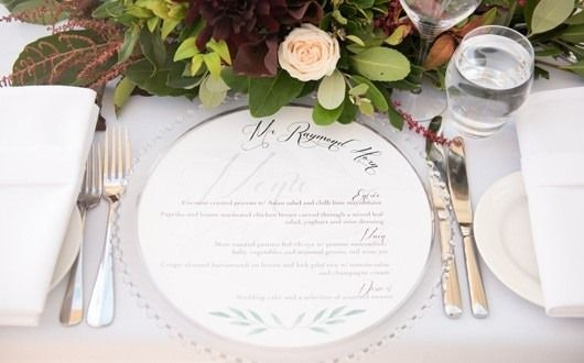 Glass charger plates with menu on top framed by greenery