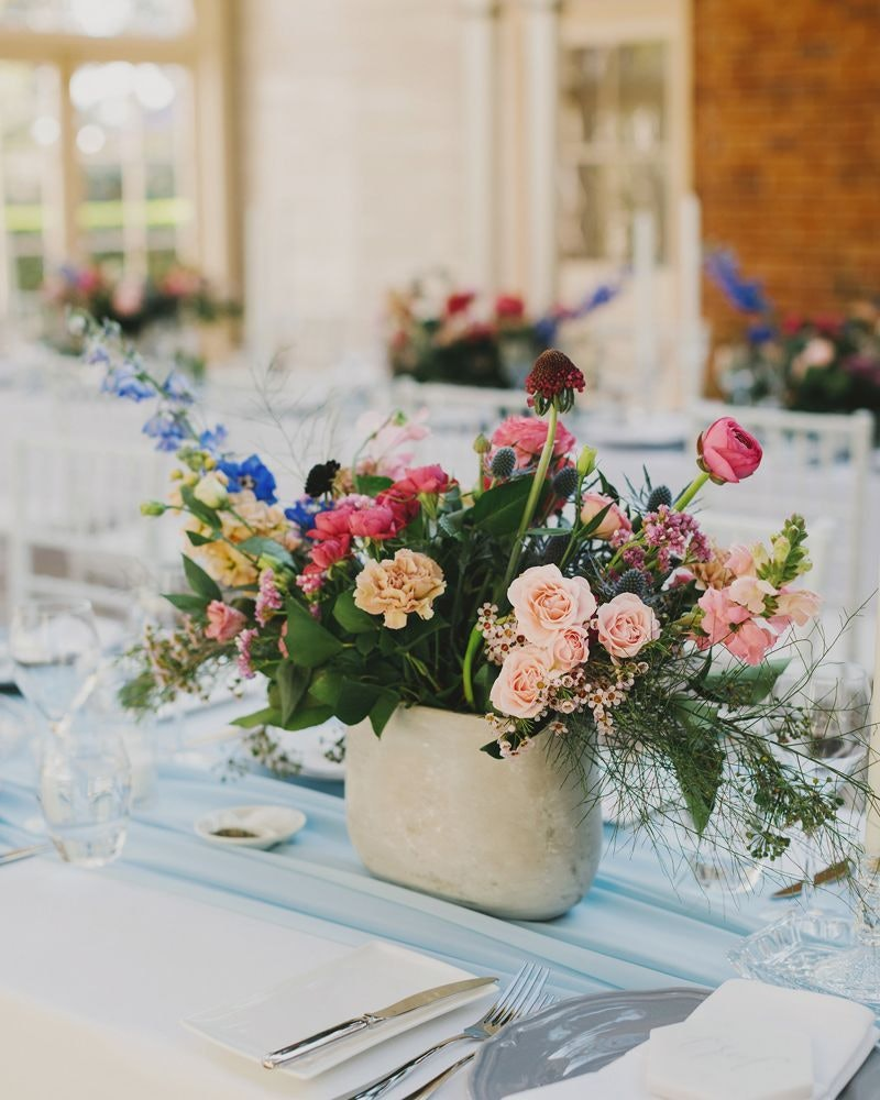 Vase of pink and blue wedding flowers on reception table