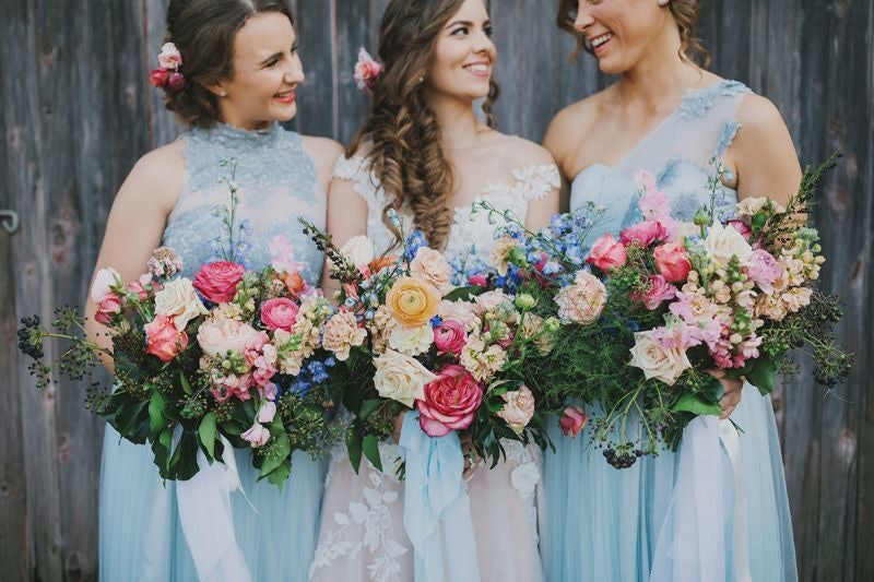 Bride and bridesmaids with beautiful bouquets of pink and blue flowers
