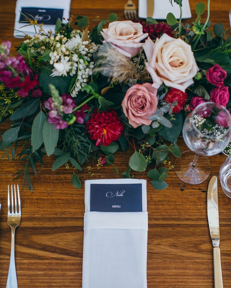 Menu tucked into white napkin with red and gold flowers