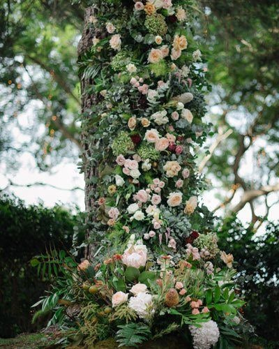 Wedding floral installation using tree trunk