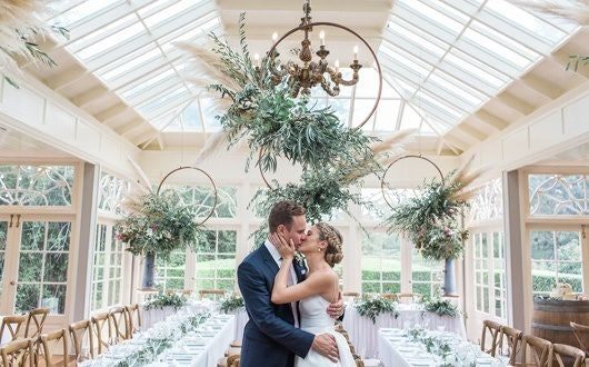 Couple kiss under greenery