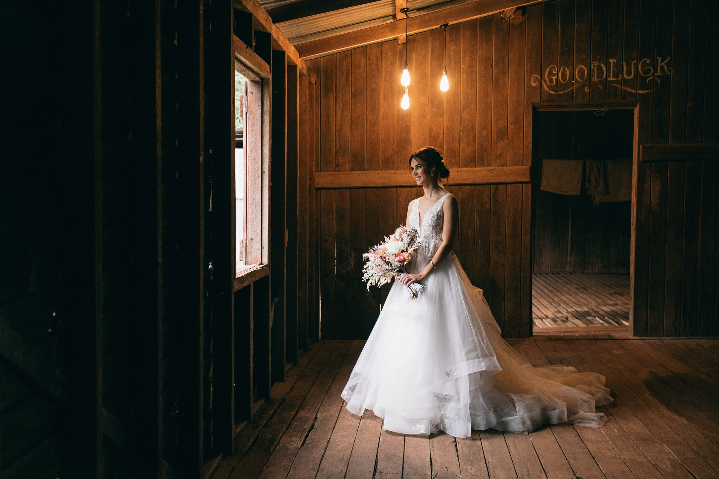 Bride in big white gown in country stables