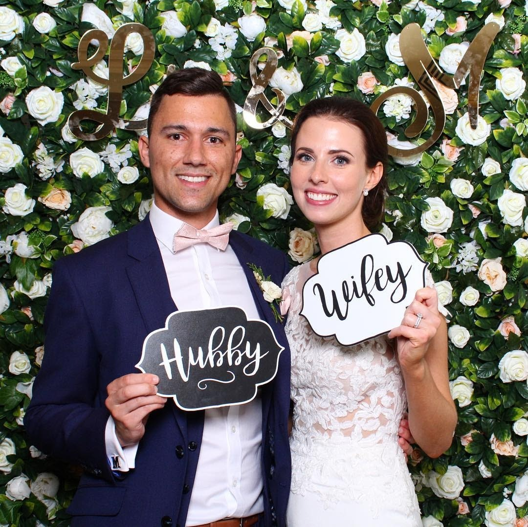 Couple pose in front of flower wall with hubby and wifey signs