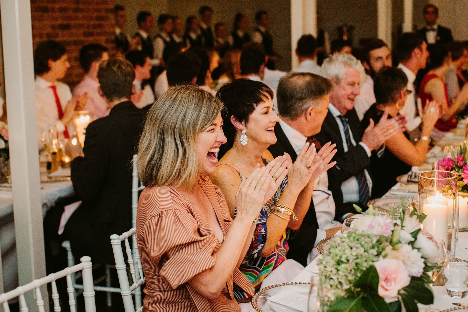 Guests laugh and clap