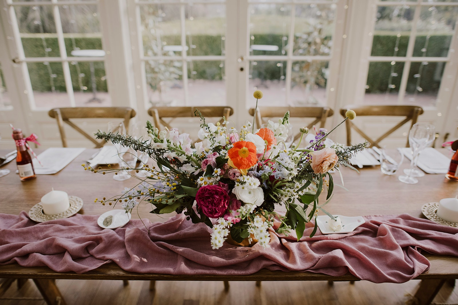 Pink and red flowers line the edge of a bridal table