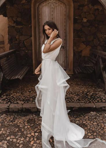 Bride with wedding dress that has sheer ruffled skirt, sweeping her hair behind her ear