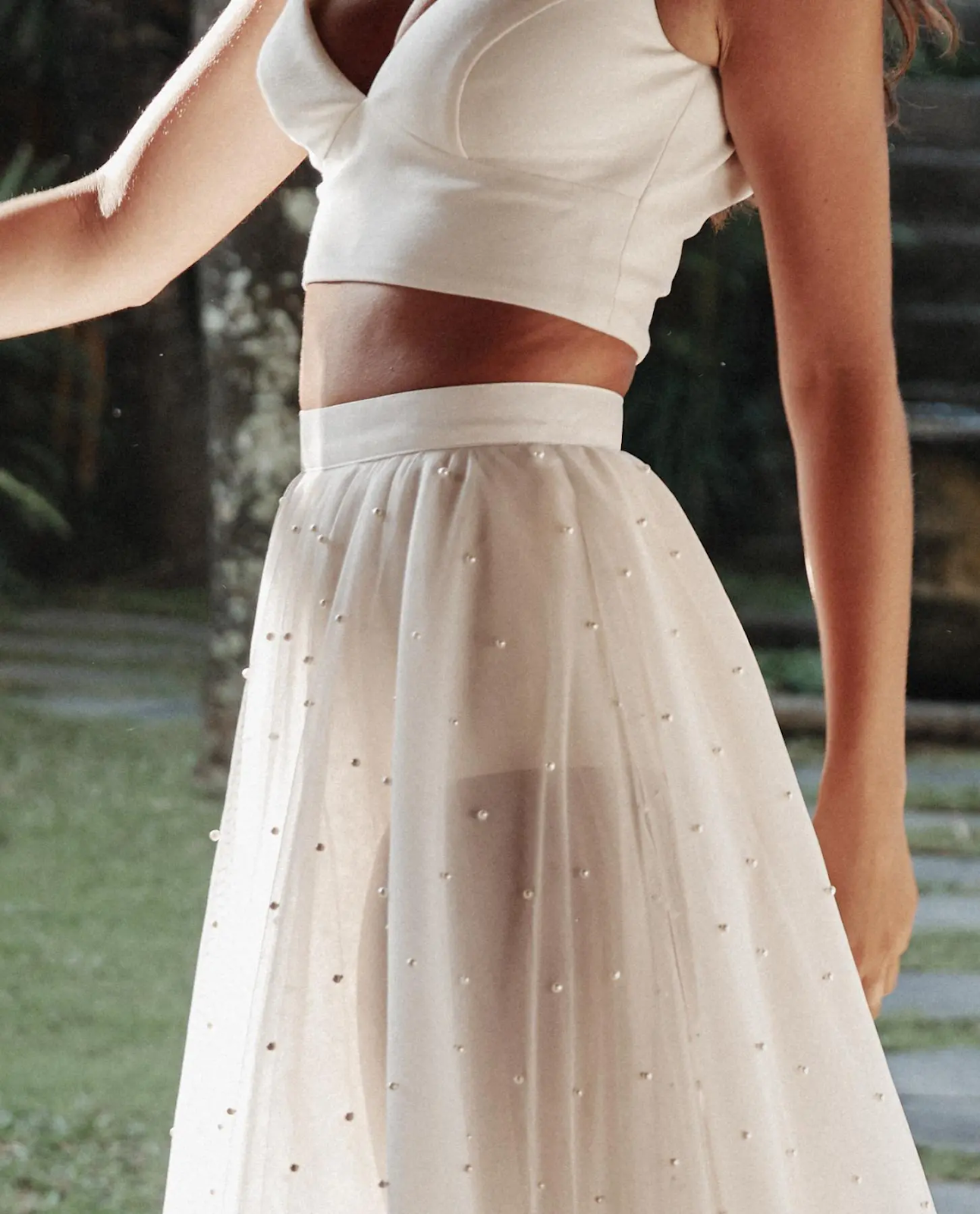 Wedding dress that has bodice top and flowing sheer skirt with mid-rift showing