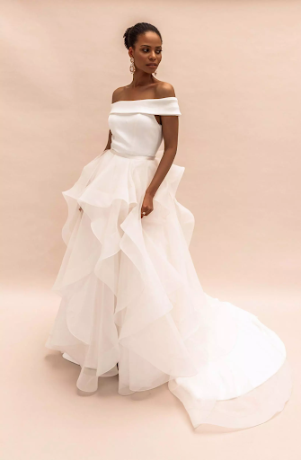 Bride with shoulderless gown with minimalist bodice and large flowing skirt with tiers