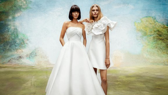 Two brides standing next to each other. One with a strapless full skirt gown the other with a short gown with oversized ruffles and short sleeves