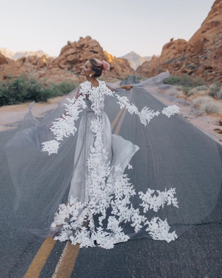 Bride is standing on a highway wearing a silver dress with a long flowing sheer cape with thick white floral applique