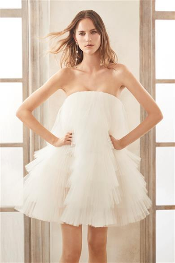 Bride is standing with her hands on hips wearing a short dress with short flowing tulle layers