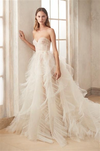 Bride is standing next to French windows wearing a fitted bodice with a flowing tulle layered skirt