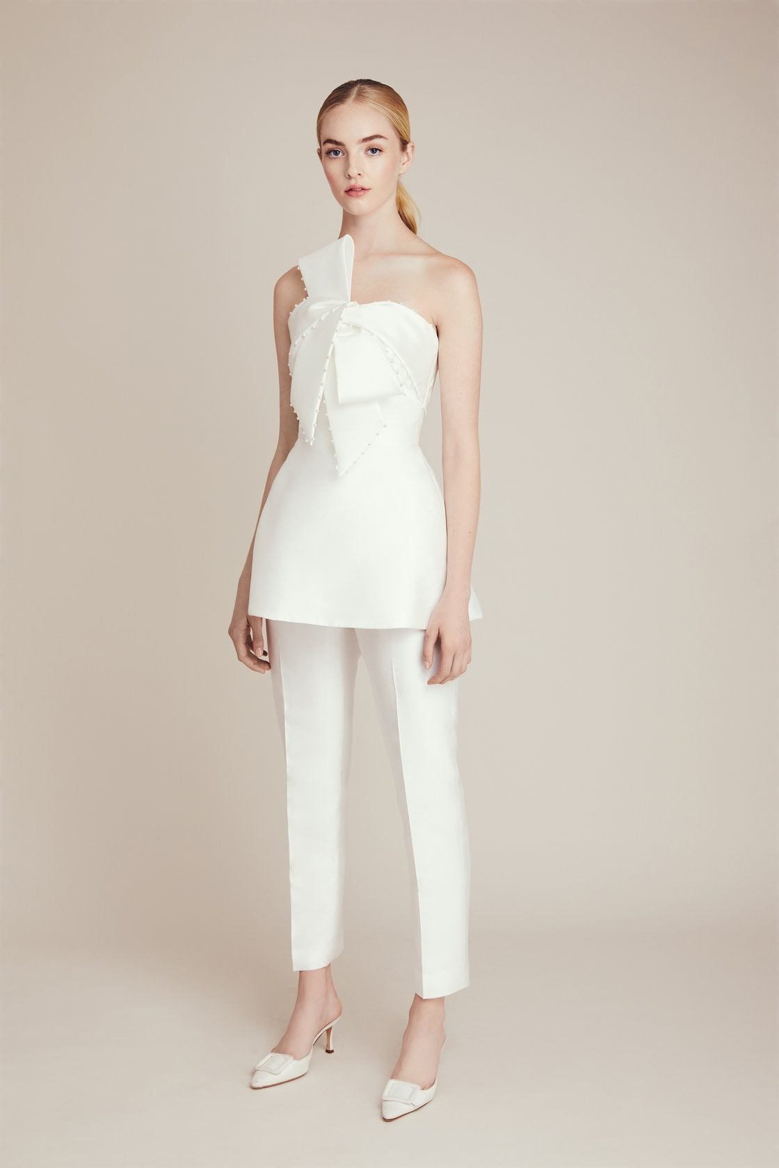 Bride is wearing cropped white pants with a peplum white shoulderless top with a bow