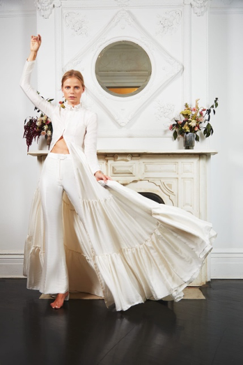Bride is posing in front of a fireplace wearing white full length pants and a button up jacket that is floor length.