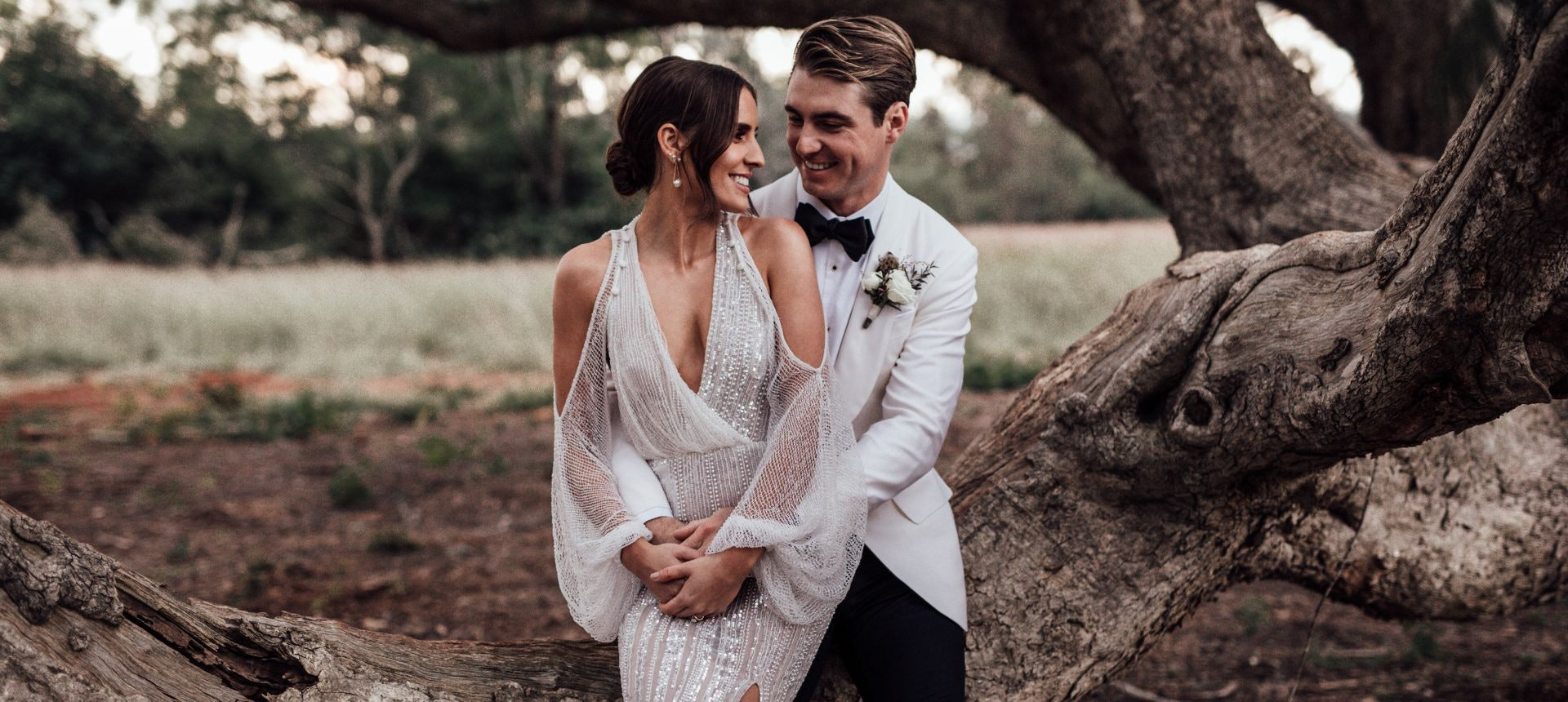 Bride is sitting on grooms lap on a tree branch