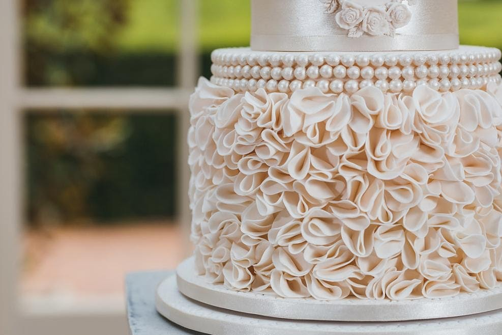 Close up shot of wedding cake with icing ruffles and white pearl icing beads on the outside