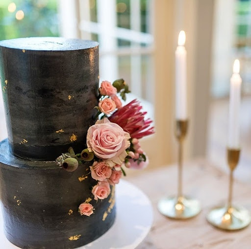 Black two-tiered wedding cake with pink roses and proteas on the side