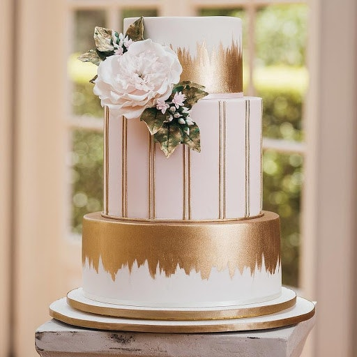 Three tiered white and gold wedding cake with white gardenia flower on the side and gold icing