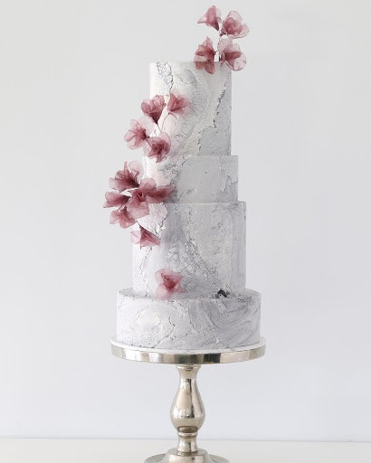 white marble texture cake with pink flowers up the side