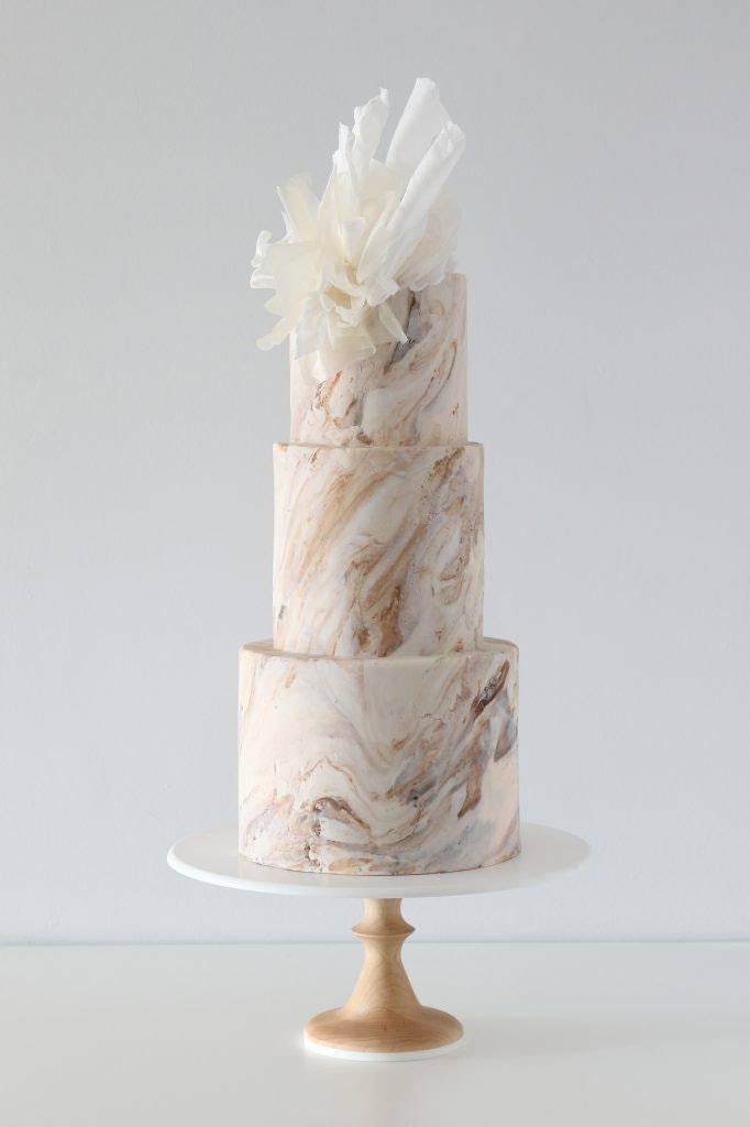 gold marble wedding cake with white tulle icing on top