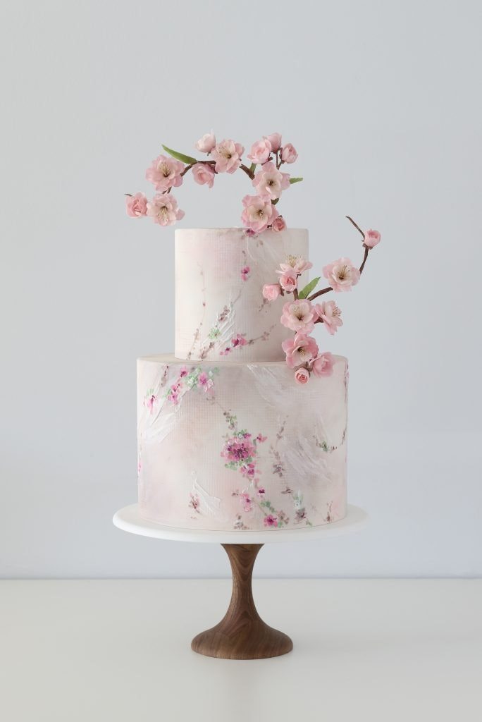 white wedding cake with handpainted pink cherry blossoms with fondant cherry blossoms