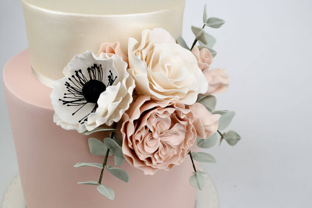 Dusty pink and silver two tiered wedding cake with carnation flowers on the side