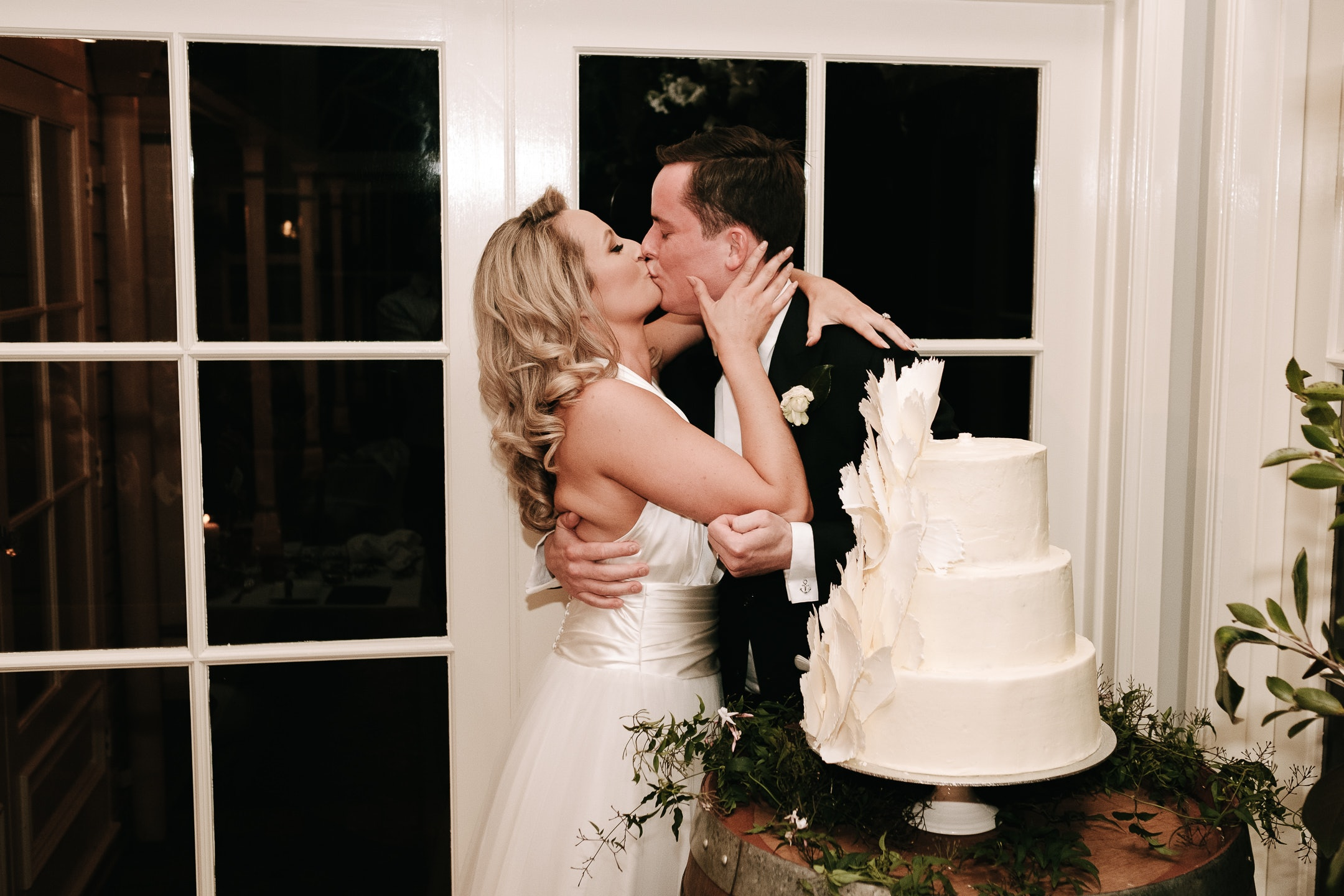 Bride and groom kissing next to wedding cake
