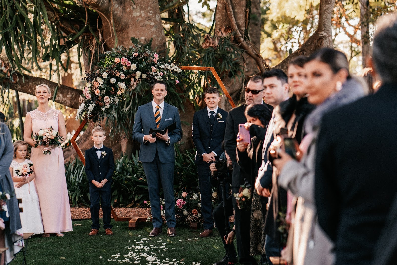 Groom standing at the end of the aisle with two children waiting for the bride to walk down